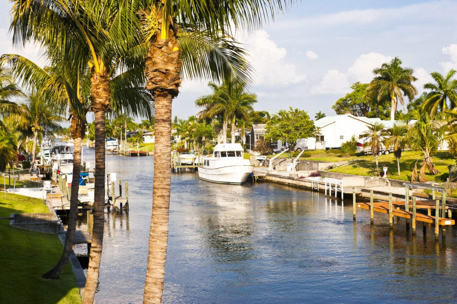 Florida living, boats docked at waterfront of luxury homes on a canal in southern Florida.