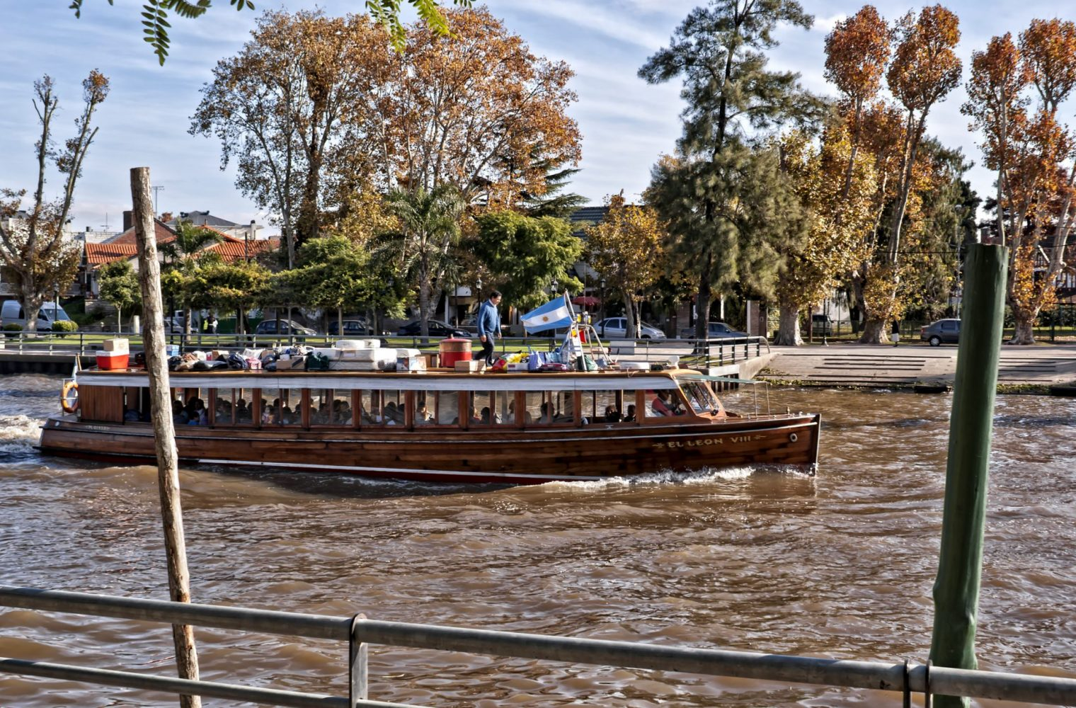A wooden passenger boat is crossing the river with baggages, flag and a person on roof. Sky with clouds, in autumn. Taken in Puerto de Frutos, is a small dock on the Lujan river, where has fruit market, region's craftwork , basketry, typical argentine food, among other things. Now, restaured, also is a touristic place for appreciate the culture of this region. On Delta of Tigre city , Buenos Aires province, Argentina.
